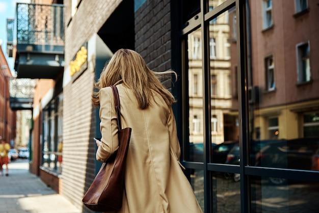 여자는 도시 거리에서 즐겁게 지냅니다. 코트를 입은 여성이 도시를 산책하다