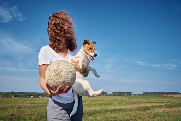 여자는 여름 날 야외에서 그녀의 강아지와 함께 재미 있습니다. 애완 동물과 우정 소유자