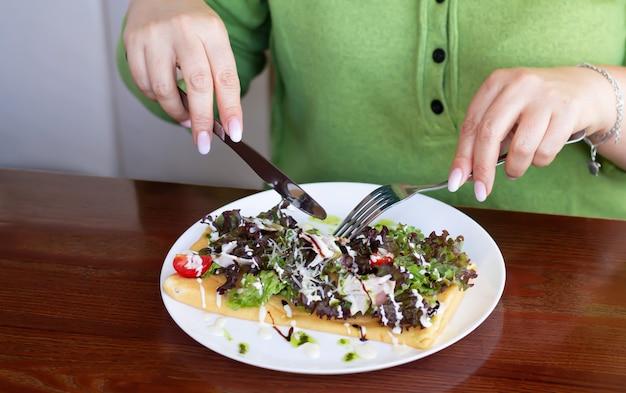 女性はカフェで昼食をとります。