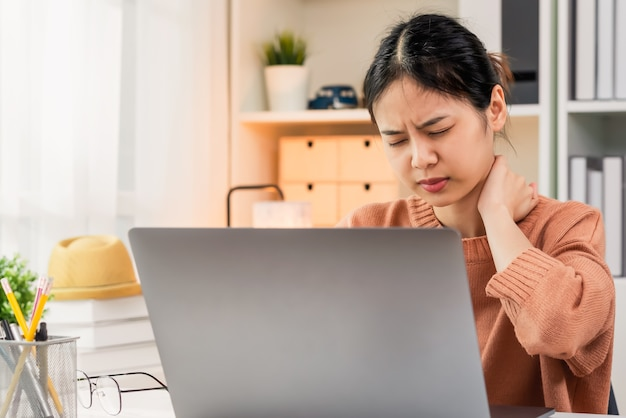 Woman have a neck pain because using the computer for a long time