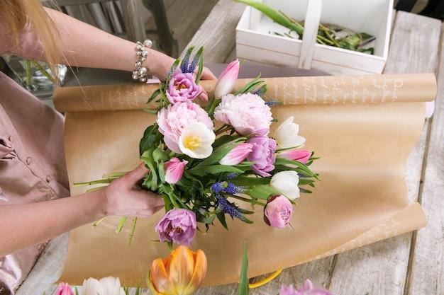 여자는 포장지 평면도에 튤립 꽃다발을 팩. 인식 할 수없는 꽃집은 나무 배경에 워크샵에서 분홍색 모란과 야생화로 꽃집을 조립합니다.