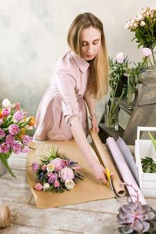 여자는 포장지에 팩 웨딩 부케가 있습니다. 젊은 아름다운 꽃집은 꽃집이 나무 배경에 워크샵에서 분홍색 모란과 야생화로 조립하게합니다.