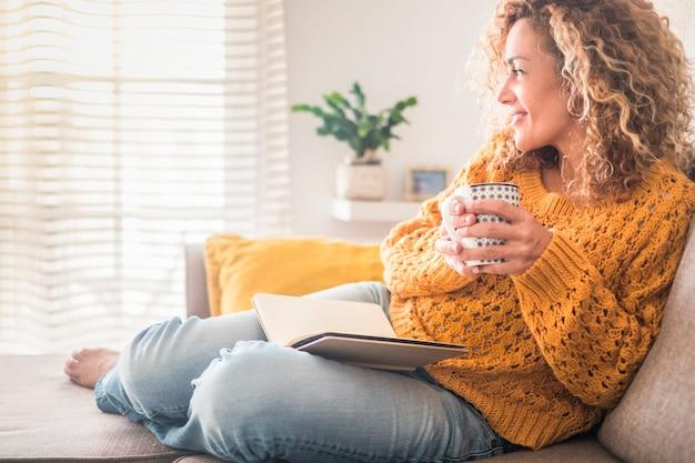 Женщина расслабиться дома с чашкой чая и книгой