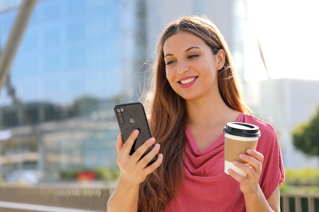 Woman have video call with smartphone while holding cup of coffee