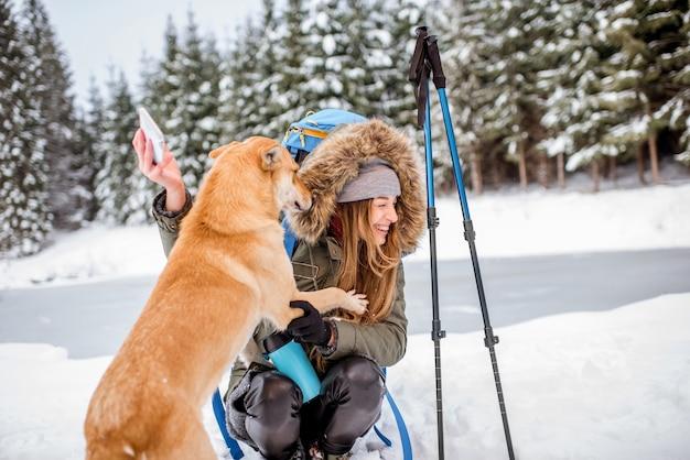 湖と森の近くの雪山で犬と一緒に自分撮りをする冬のハイキング中に休憩をとっている女性