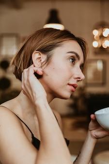 居間でコーヒーを飲んでいる女性