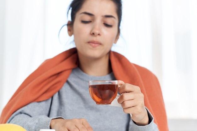 一杯のお茶の薬で風邪をひいている女性は健康上の問題を治療します