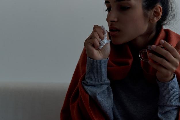 自宅でお茶の治療で風邪をひいている女性
