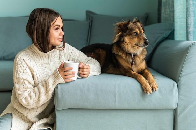유행병 동안 집에서 그녀의 개 옆에 커피 한 잔을 마시는 여자
