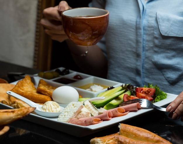 お茶、朝食用食品を持つ女性
