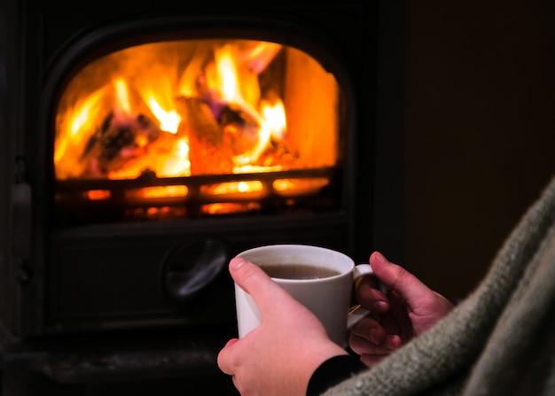 暖炉のそばでスケートリンクの熱いカップを持っている女性。