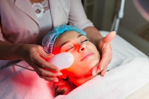Женщина, проходящая лечение кожи лазером в клинике по уходу за кожей