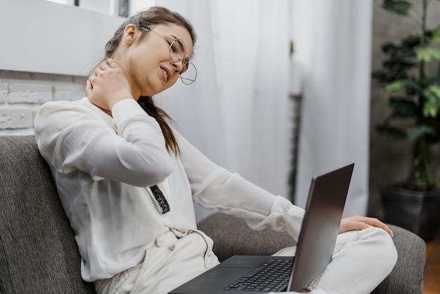 Женщина, у которой болит шея, работает дома