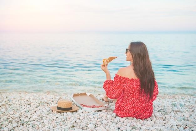 ビーチでピザとピクニックを持つ女性