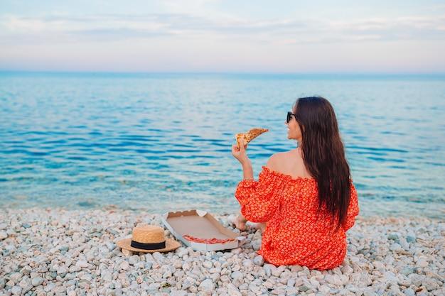 ビーチでピザとピクニックをしている女性