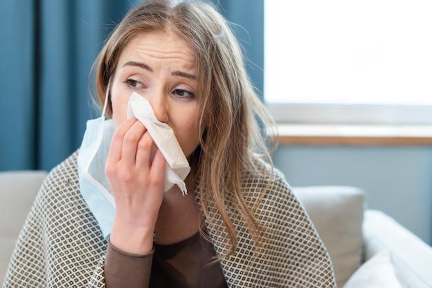 屋内で鼻水を持つ女性