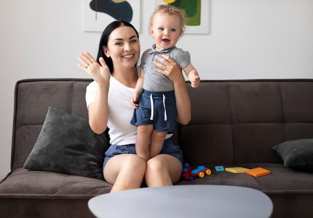Женщина разговаривает по видеосвязи со своей семьей, держа ребенка на руках
