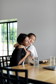 屋内で娘の隣で夫とビデオ通話をしている女性