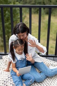屋外で娘の隣で夫とビデオ通話をしている女性