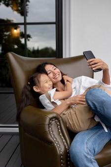 야외에서 딸 옆에서 남편과 영상 통화를 하는 여성
