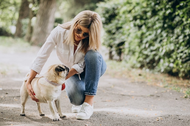 パグ犬ペットと公園で散歩を持つ女性