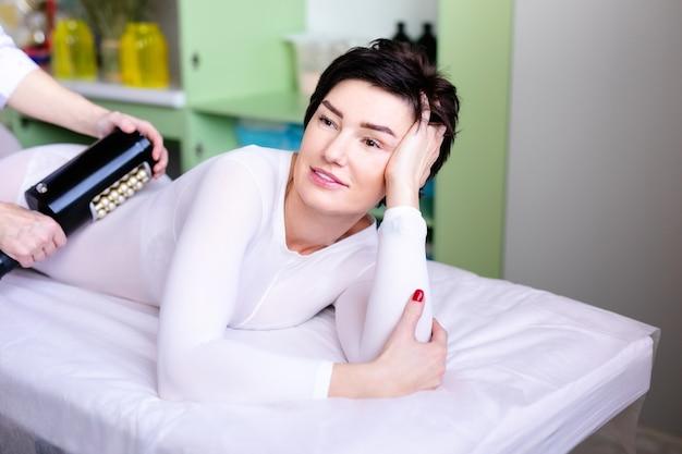Woman having anti-cellulite lpg or r-sleek massage treatment with apparatus in beauty salon.
