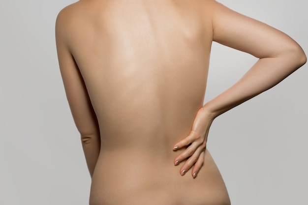 요통이 있는 여자, 통증은 회색 배경에 격리되어 있습니다. 척추 측만증. 여성의 등에 척수 문제. 그녀의 등을 만지고 아름 다운 벌 거 벗은 여자.