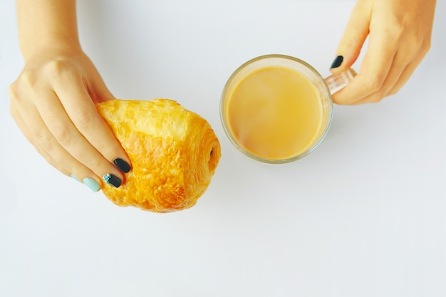 Woman having breakfast french croissant and coffee on a white table