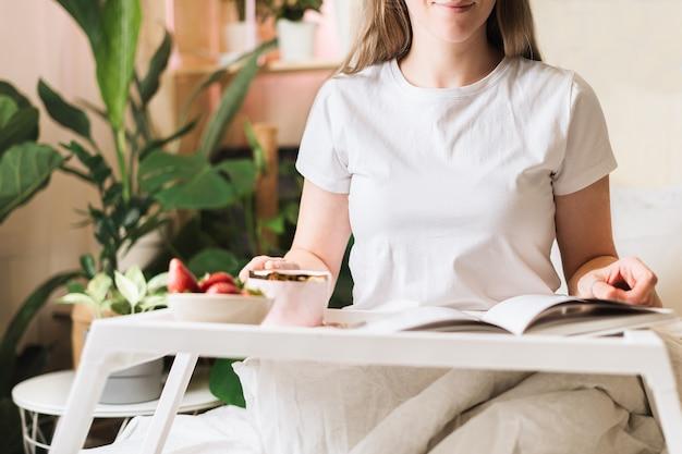 Женщина, завтракающая в постели с кофе и клубникой.