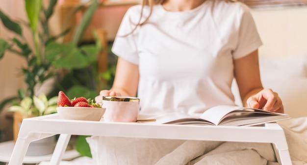 Женщина завтракает в постели с клубникой.