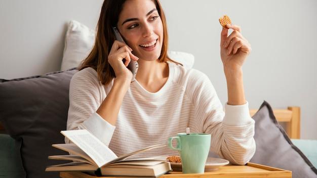 Donna che fa colazione e parla al telefono a casa
