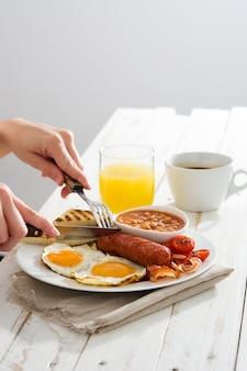 Woman having breakfast traditional full english breakfast on wooden surface
