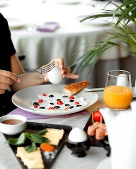 ゆで卵と卵黄で朝食を食べている女性、トマトとオリーブで調理