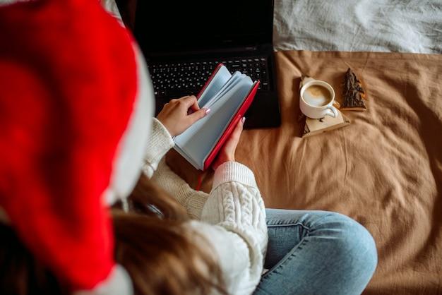 ベッドでコーヒーラテのカップで朝食を食べている女性。居心地の良い週末。