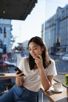 여자 카푸치노 있고 휴대 전화 채팅