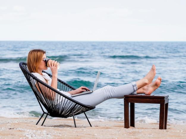 ラップトップに取り組んでいる間ビーチでコーヒーを飲んでいる女性