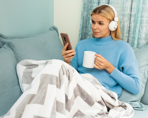 Женщина пьет кофе дома, используя смартфон и наушники во время пандемии