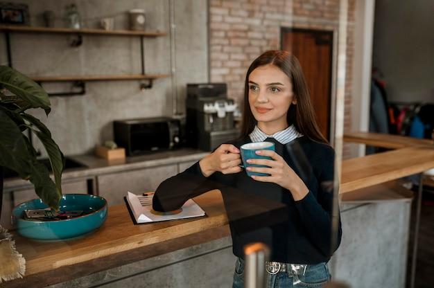 Donna che mangia caffè durante una riunione