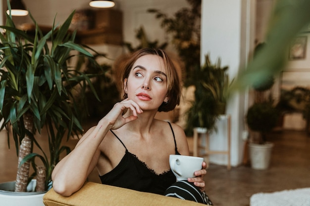 Woman having a coffee in her living room