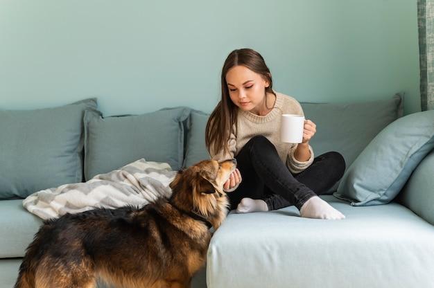 Donna che mangia un caffè a casa con il suo cane durante la pandemia