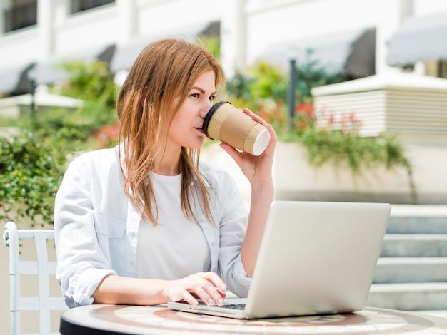 Женщина, имеющая кофе на открытом воздухе во время работы на ноутбуке