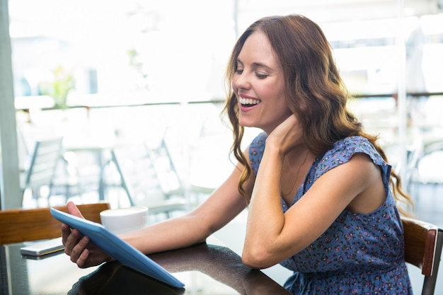 Woman having coffee and using her tablet