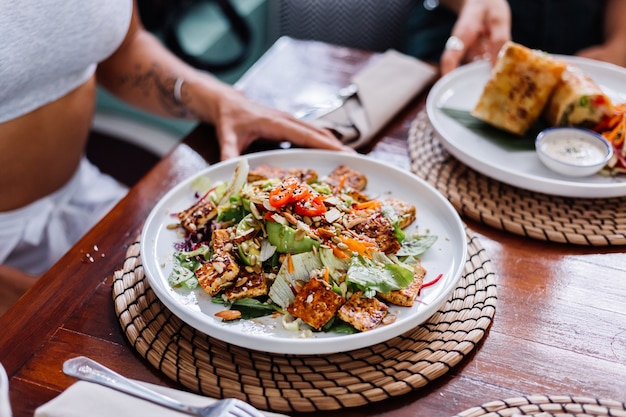 夏のカフェ自然光でカラフルな健康的なビーガンベジタリアンミールサラダを持っている女性