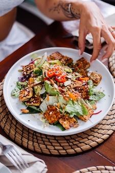 Donna che mangia insalata di pasto vegetariano vegano sano colorato nella luce del giorno naturale del caffè estivo