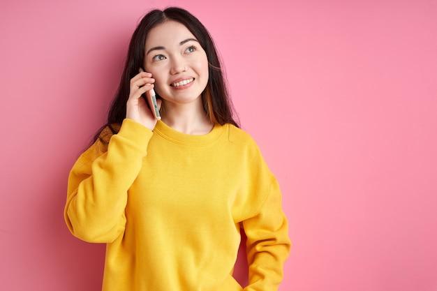 電話で友人と会話、素敵な話、カジュアルな服を着て、横を見て、ピンクの背景で隔離の女性