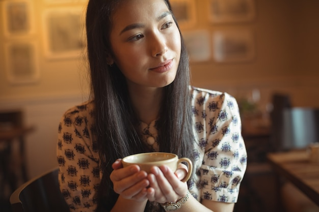Woman having cup of coffee at cafe