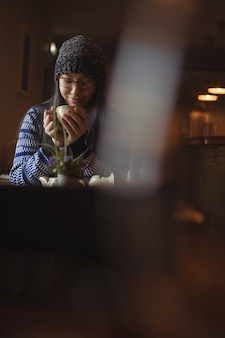 Donna che mangia una tazza di caffè nella caffetteria