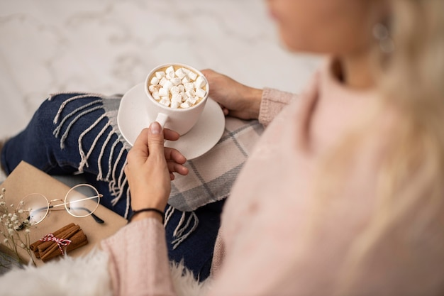 Woman having cup of hot cocoa with marshmallows while reading