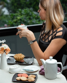 Woman having a cup of tea with pastry.