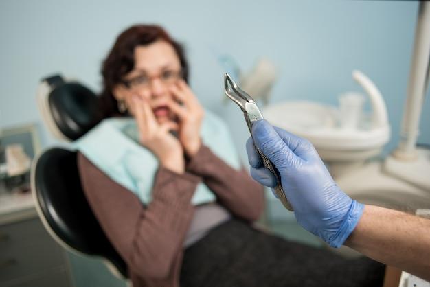 Женщина, имеющая стоматологический осмотр в стоматологическом кабинете